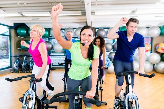 Gruppe von männern und frauen, die auf fitnessfahrrädern im fitnessstudio drehen