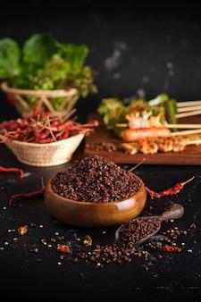Gruppe von mala gegrilltem grill (bbq) mit sichuan-pfeffer, scharfem und würzigem und leckerem street food auf holzbrett und zutaten (chili, sichuan-pfeffer, knoblauch)