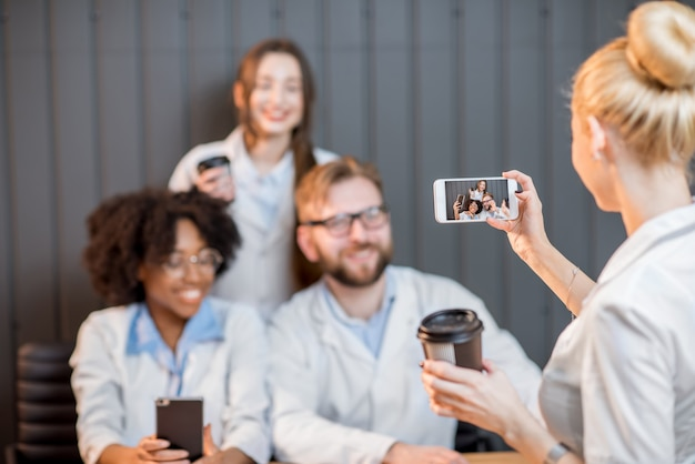 Gruppe von medizinstudenten, die während der kaffeepause im klassenzimmer spaß beim fotografieren mit telefonen haben
