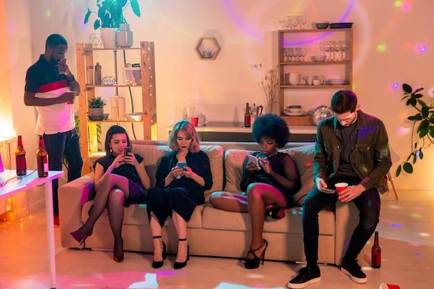Gruppe von mehreren jungen freunden verschiedener ethnien, die in mobilen geräten scrollen, während sie neue beiträge durchsehen oder kommentare schreiben