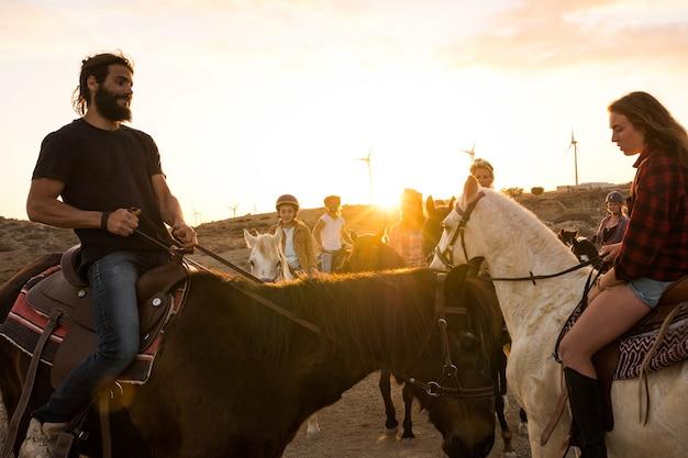 Gruppe von menschen, die bei sonnenuntergang in den hügeln zusammen pferde reiten - aktive und glückliche menschen, die spaß haben und mit tieren spielen oder spazieren gehen - cowboy und cowgirl auf einer ranch