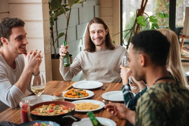 Gruppe von menschen, die beim abendessen bier und wein trinken