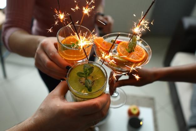 Gruppe von menschen, die cocktails mit wunderkerzen in den händen halten