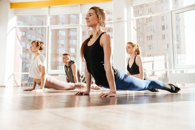 Gruppe von menschen, die dehnübungen machen und yoga praktizieren