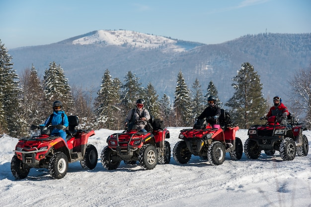 Gruppe von menschen, die im winter quad-bikes auf schnee oben auf dem berg fahren