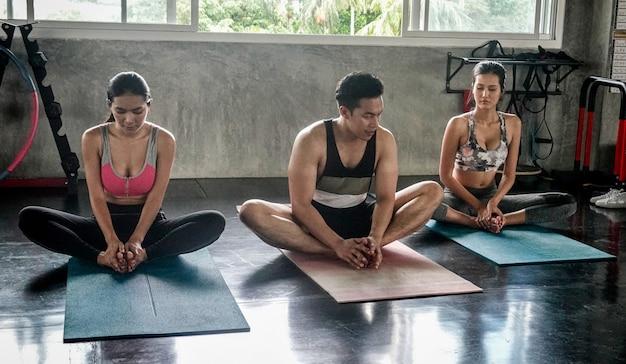 Gruppe von menschen, die yoga-übungen im studio machen