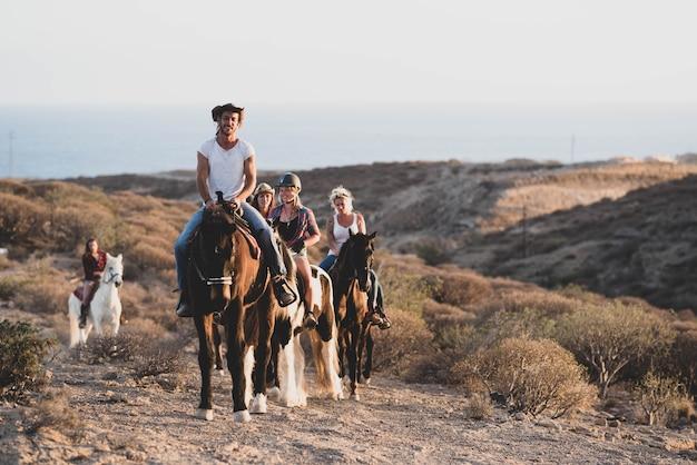 Gruppe von menschen, die zusammen auf einem pferd reiten und neue orte entdecken - reitunterricht lernen - cowboy-konzept und lebensstil - aktive menschen, die spaß haben und mit tieren sport treiben
