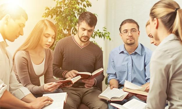 Gruppe von menschen, die zusammen ein bibelbuch lesen