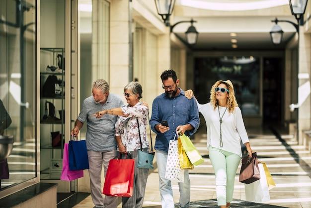 Gruppe von menschen, die zusammen im einkaufszentrum einkaufen gehen und einkaufstüten halten - zwei senioren und ein paar erwachsene, die geschäfte suchen