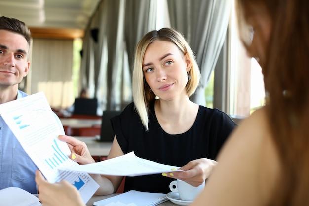Gruppe von menschen halten in waffen finanzpapiere zu lösen