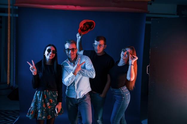 Gruppe von menschen in freizeitkleidung und brille steht und hat spaß drinnen im studio mit neonbeleuchtung.