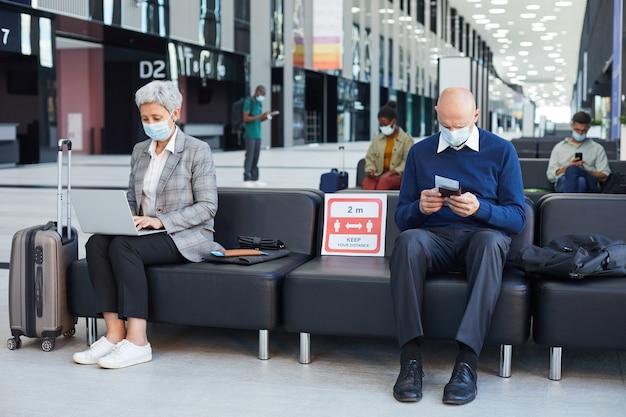 Gruppe von menschen in masken, die im wartezimmer sitzen und soziale distanz halten