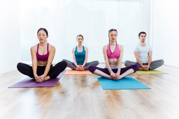 Gruppe von menschen praktizieren yoga zu hause. baddha konasana pose