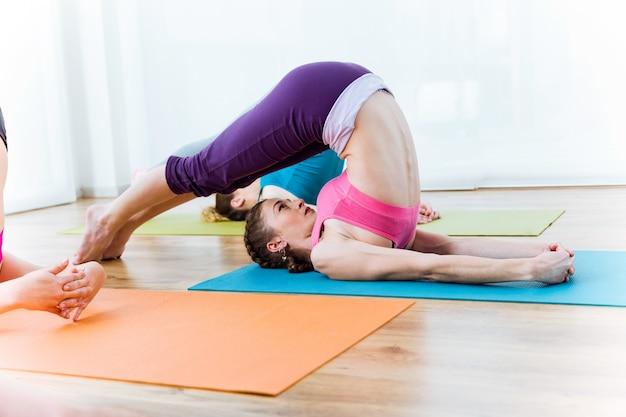 Gruppe von menschen praktizieren yoga zu hause. halasana-pose