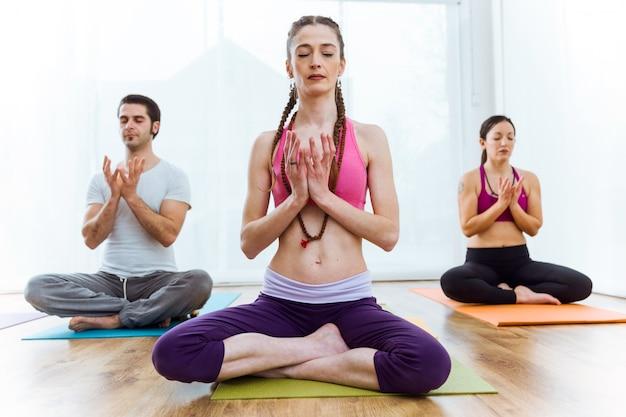 Gruppe von menschen praktizieren yoga zu hause in der lotus-position.