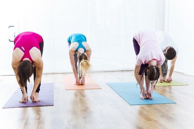 Gruppe von menschen praktizieren yoga zu hause. uttanasana-pose
