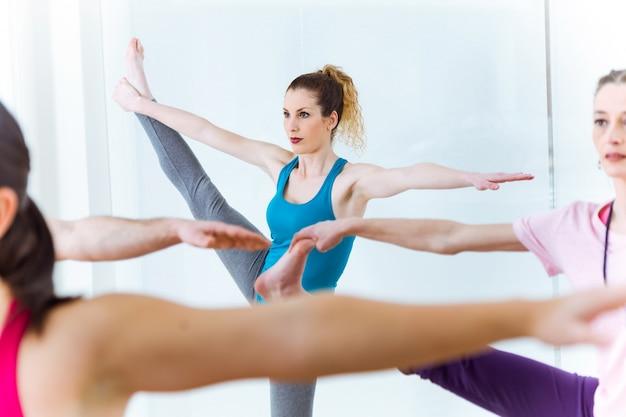 Gruppe von menschen praktizieren yoga zu hause. utthita hasta padangushtasana pose