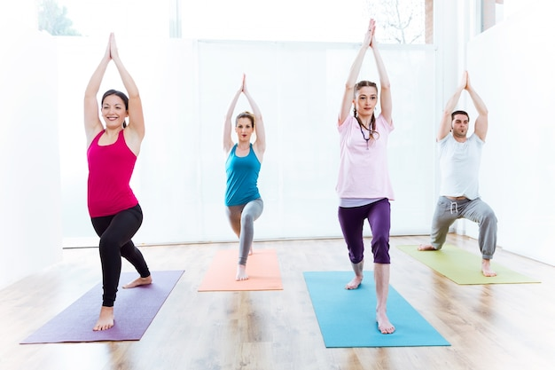 Gruppe von menschen praktizieren yoga zu hause. virabhadrasana posieren