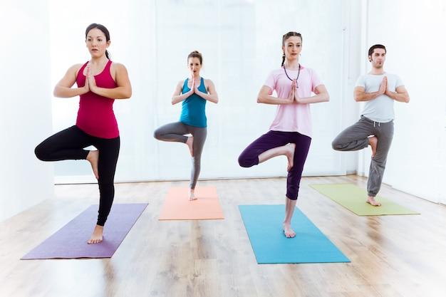 Gruppe von menschen praktizieren yoga zu hause. vrksasana pose