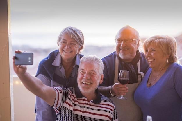 Gruppe von menschen senioren kaukasier, die spaß haben, gemeinsam draußen zu hause auf der terrasse mit blick auf das dach zu feiern. fotografieren selfie mit telefontechnologie lächelnd und lachend vor freude. essen