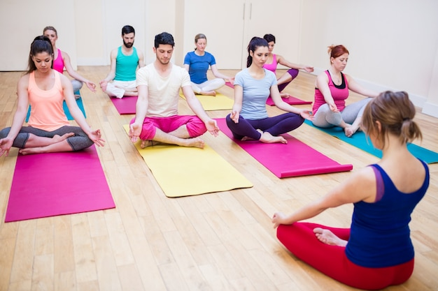 Gruppe von menschen und trainer sitzt im lotussitz