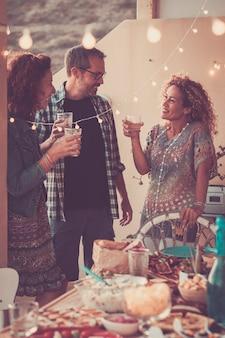 Gruppe von menschenfreunden genießen die cocktail-happy-hour-zeit zu hause oder in der kneipe im freien - genießen sie die freundschaft für erwachsene männer und frauen zusammen in freundschaft vor einem tisch voller essen zum abendessen