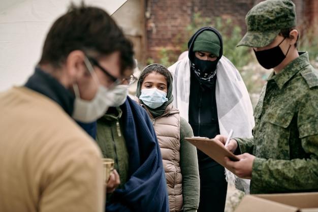 Gruppe von migranten in schutzmasken, die auf spende warten