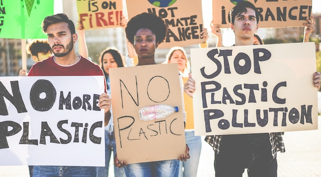 Gruppe von millennials demonstranten auf der straße, junge menschen aus verschiedenen kulturen und rassen kämpfen für plastikverschmutzung und klimawandel - konzept der globalen erwärmung und umwelt - fokus auf gesichter