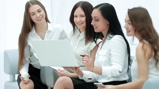 Gruppe von mitarbeitern, die einen laptop verwenden, um finanzdaten zu überprüfen