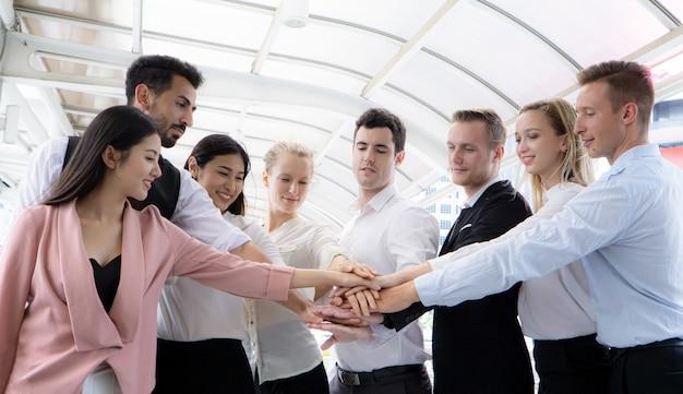 Gruppe von mitarbeitern, die hände zusammensetzen