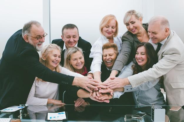 Gruppe von mitarbeitern, die ihre handflächen über den schreibtisch legen. das konzept der teamarbeit