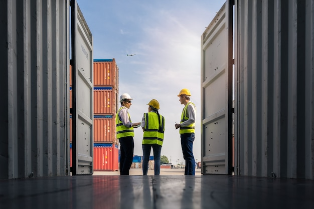Gruppe von mitarbeitern, die stehen und die containerbox vom frachtschiff für den export und import überprüfen Premium Fotos