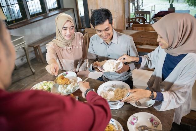 Gruppe von mitarbeitern, die zusammen zu mittag essen, während sie sich mit freunden im speisesaal treffen