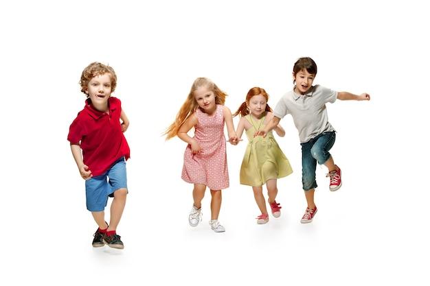 Gruppe von modebewussten kindern im vorschulalter, die zusammen laufen und in die kamera schauen