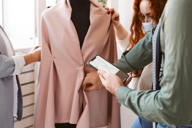 Gruppe von modedesignern, die im atelier arbeiten und kleidungsstücke auf kleiderform überprüfen