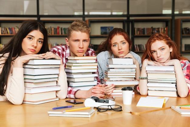 Gruppe von müden teenagern, die an der bibliothek sitzen