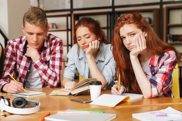 Gruppe von müden teenagern, die hausaufgaben machen
