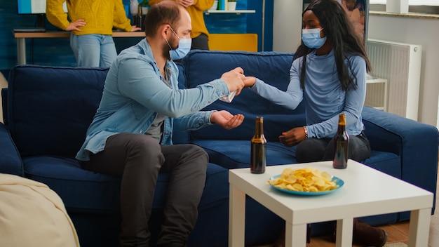 Gruppe von multiethnischen, die händedesinfektionsgel verwenden, um zu verhindern, dass sich covid19 ausbreitet und zeit zusammen im wohnzimmer auf einem sofa mit gesichtsmaske verbringt. diverse menschen, die kontakte knüpfen und soziale distanz wahren