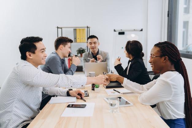 Gruppe von multikulturellen geschäftsleuten, die ihre chefrede hören, asiatischer mannmanager, der mit seinem team spricht