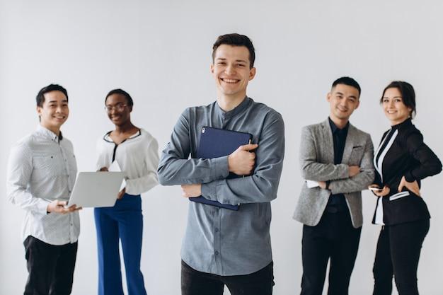 Gruppe von multikulturellen jungen führungskräften, die stehen und damit beschäftigt sind, smartphones für die arbeit im büro zu verwenden. social media technologie und online-geschäft mit teenager-lifestyle-konzept