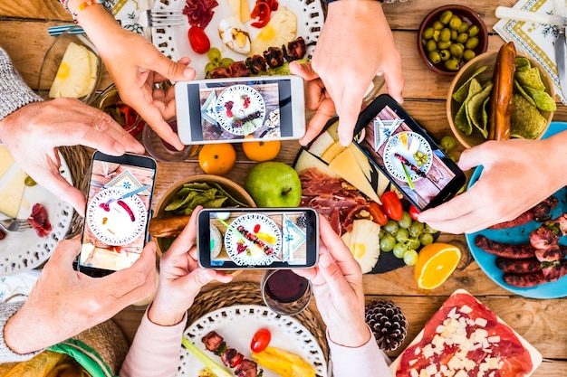 Gruppe von nicht erkennbaren freunden oder kaukasischen familienmitgliedern, die zusammen spaß haben, um ihre gerichte mit essen zu fotografieren