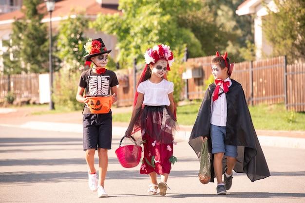 Gruppe von niedlichen freundlichen kindern in halloween-kostümen und farben, die sich unterhalten, während sie sich die straße zwischen landhäusern hinunterbewegen