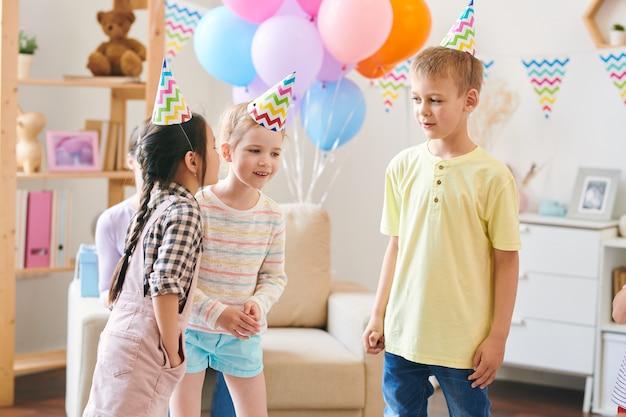 Gruppe von niedlichen kleinen kindern in geburtstagskappen, die regeln des neuen spiels besprechen, während spaß zu hause party in dekoriertem raum haben