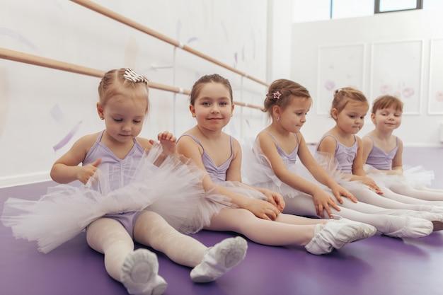 Gruppe von niedlichen kleinen mädchen, die ballett-tutus tragen, die auf dem boden im tanzstudio sitzen