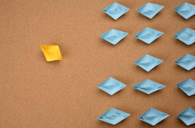 Gruppe von papierbooten auf einer braunen oberfläche. konzept einer starken führungskraft im team, manipulation der massen, verfolgung neuer perspektiven, zusammenarbeit und vereinigung. anlaufen