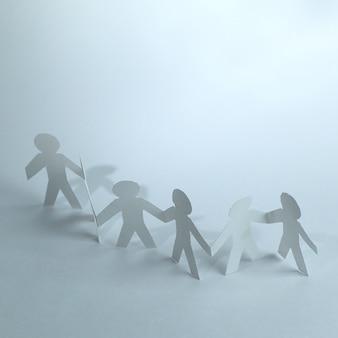 Gruppe von papiermännern, die sich gegenseitig die hände halten. das konzept der zusammenarbeit
