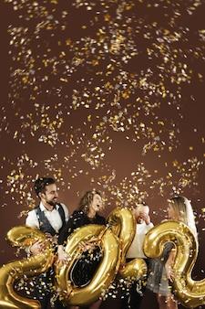 Gruppe von partyleuten, die die ankunft des neuen jahres 2022 mit goldenen ballons und fallendem konfetti feiern