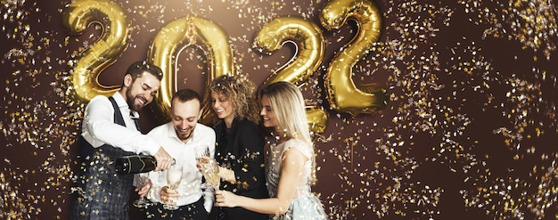 Gruppe von partyleuten, die die ankunft des neuen jahres 2022 mit goldenen luftballons und fallendem konfetti feiern, die sekt trinken