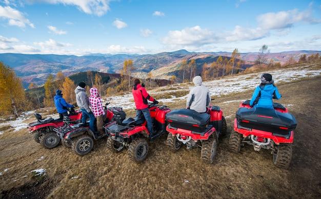 Gruppe von personen auf roten quad-bikes