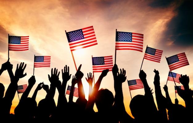 Gruppe von personen, die amerikanische flaggen in gegenlicht wellenartig bewegt